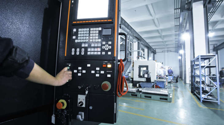 workers operating the controls of a CNC machine that manufactures parts for the aerospace Industry.